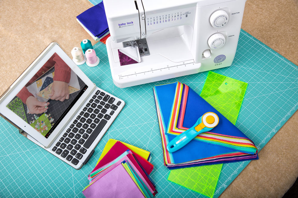 A tablet with keyboard displays an online quilting class with an image of a modern white sewing machine, quilt tools, thread, and a quilting kit on a gridded cutting mat.